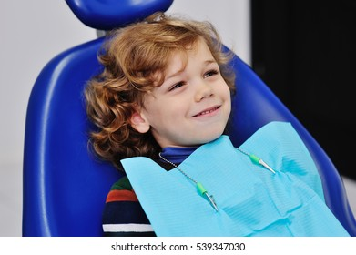 cheerful child boy with curly red hair in blue dental chair smiling
