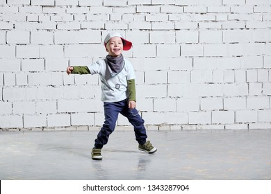 cheerful child boy dancing to music. Cool boy hip hop. Cute fashionable kid. Little rapper man wears a cap, sneakers, pants, t-shirt, street style clothes. studio, brick wall background.