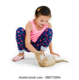 cheerful child girl plays with a little kitten on a light background