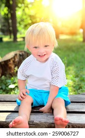 Cheerful Child on the Bench at the Summer Park