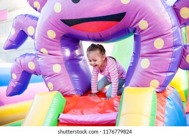 A cheerful child plays in an inflatable castle