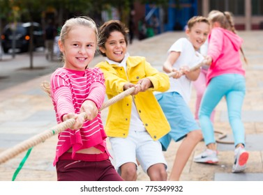 Cheerful children are competing and tug of war on the playground.
