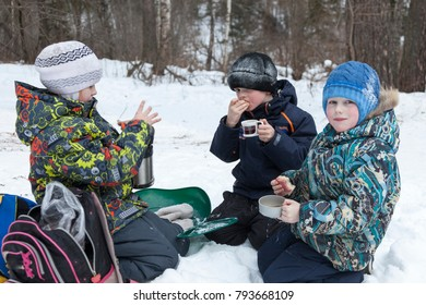 cheerful children eat for a walk in winter