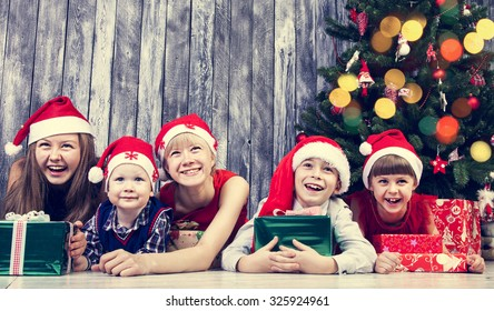 Cheerful children with gifts next Christmas tree