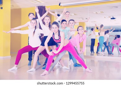 Cheerful children having fun in a choreography class, posing with female trainer