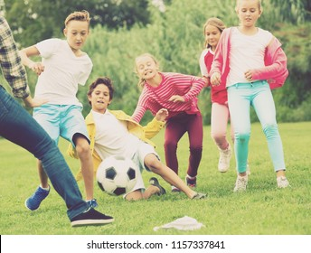 Cheerful children are jogning with ball on the playground.