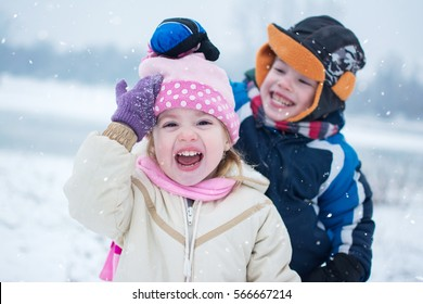 Cheerful children playing on snowy winter day. Little boy taking off hat from cute little girl.