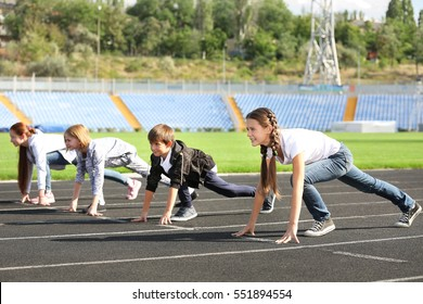 Cheerful children in ready position to run on track