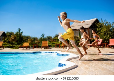 Cheerful children rejoicing, jumping, swimming in pool.