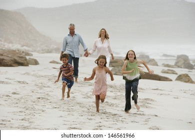Cheerful children running on beach with parents walking in background
