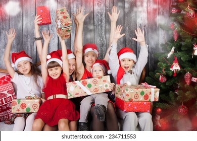 Cheerful children in santa cluas hats holding Christmas presents