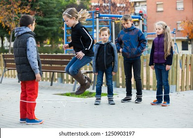 Cheerful children skipping on chinese jumping elastic rope in yard