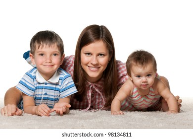 A cheerful children with smiling mother are lying on the white carpet
