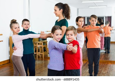 Cheerful children studying of partner dance  at dance school
