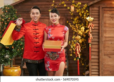 Cheerful Chinese couple with gifts for Spring Festival