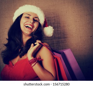 cheerful christmas woman in santa's hat smiling and holding shopping bags over canvas background, toned