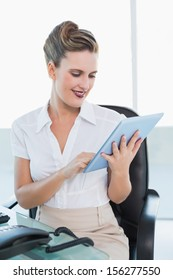 Cheerful classy businesswoman using her digital tablet in bright office