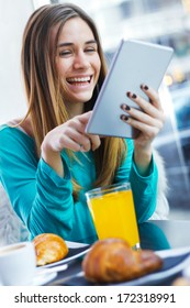 Cheerful classy woman using tablet while having breakfast in coffee shop