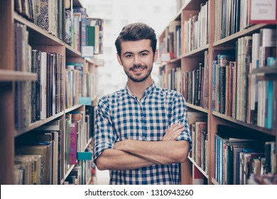 Cheerful clever young attractive brunet bearded student bookworm is standing with crossed hands in the ancient university library, between book shelves, smiling, wearing casual checkered shirt