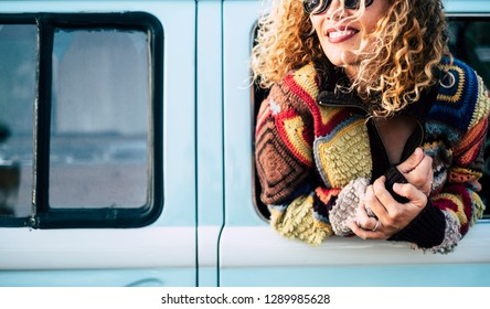 Cheerful close up portrait beautiful caucasian woman out of the van window during travel vacation - smile and enjoy modern hippy lifestyle - colors and joy concept for middle age people