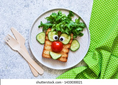 Cheerful clown. Sandwich for children for breakfast. View from above.