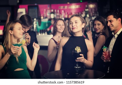 Cheerful colleagues dancing on corporate party with cocktails in hands