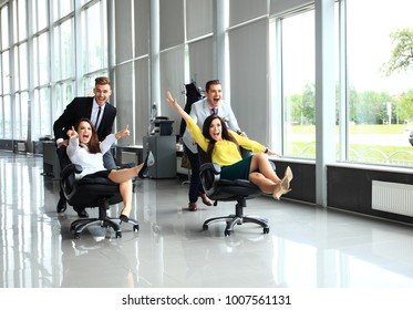 Cheerful colleagues having fun in office chairs