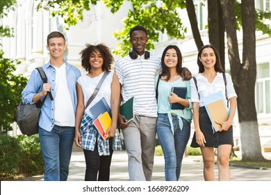Cheerful college students walking out of campus together, and posing at camera outdoors, having break in classes, free space