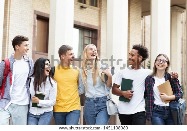 Cheerful college students walking together after study, resting in campus