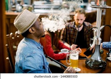 Cheerful company of friends, drinking beer and smoking hookah in shisha lounge. Rest in hookah, African man makes tornado out of smoke shisha