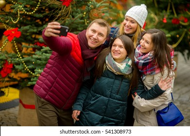 Cheerful company of young people makes selfie at Christmas fair. At foursome excellent mood. All smile. Against the background of beautifully decorated Christmas tree. Happy New Year. Merry Christmas.