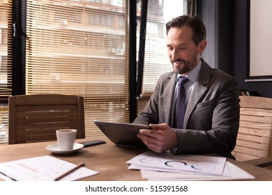Cheerful confident businessman looking at the tablet