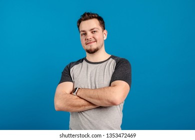 Cheerful confident handsome young man look on camera and smile. Isolated on blue background.