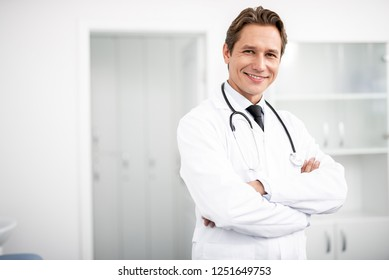 Cheerful confident young doctor in white uniform smiling and looking while standing with his arms crossed