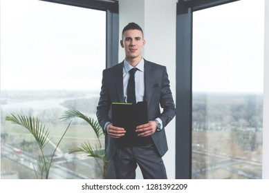 Cheerful confident young trainee in law firm standing in an office and posing ready to learn and work