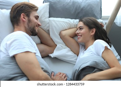 Cheerful couple awaking and looking at each other in bed.