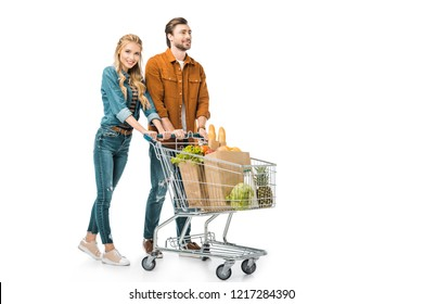 cheerful couple carrying shopping trolley with products isolated on white
