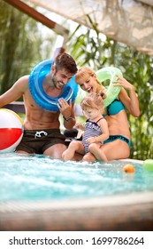 Cheerful couple with child in swimming pool