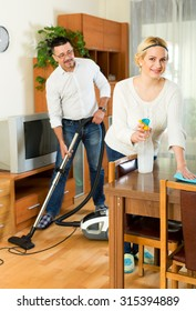 Cheerful couple cleaning in house together and smiling