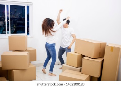 Cheerful couple dancing near piles of cardboard boxes with happy expression after moving into their new apartment