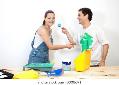 Cheerful couple doing mischief with paint