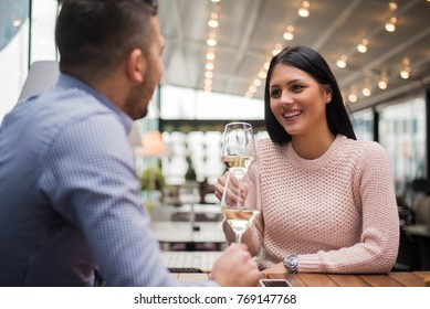 Cheerful couple drinking wine in cafe and having conversation.