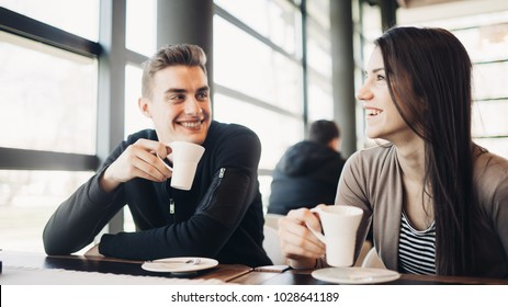 Cheerful couple enjoying coffee together in modern cafe.Drinking hot caffeine beverage on a break with business partner.Friend meeting for coffee downtown.Smiling happy people.Funny conversation