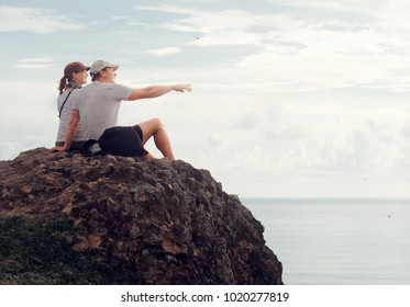 Cheerful couple enjoying the company of each other on top of the hill plan trip to distant islands looking view on ocean.Enjoy each other's company on vacation.