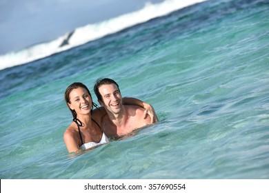 Cheerful couple enjoying sea bath in Caribbean island