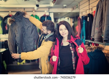 Cheerful couple examining windcheaters in sports clothes shop