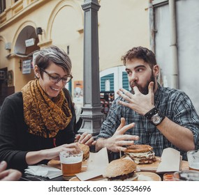 Cheerful Couple In Fast Food Restaurant Eating Burgers