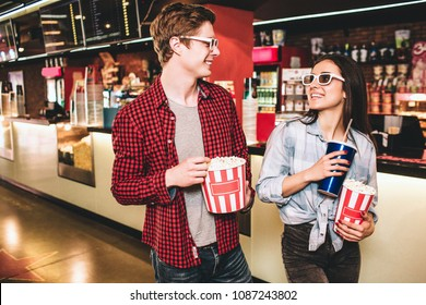 Cheerful couple in glasses are looking to each other and smiling. They are posing. Girl has a cup of coke and a basket of popcorn while guy is holding only basket of popcorn.