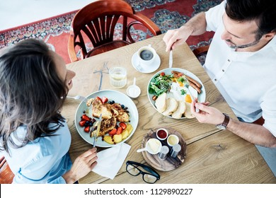 Cheerful couple having breakfast in cafe and talking. People eating together