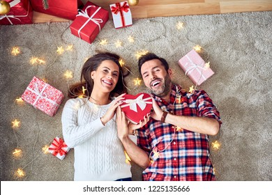 Cheerful couple having fun during christmas. Lying on floor decorated with lights and sharing presents
